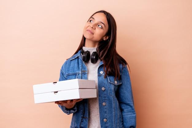 Jovem mestiça segurando uma pizza isolada, sonhando em alcançar objetivos e propósitos