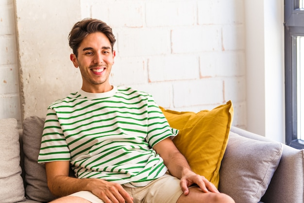 Jovem mestiço assistindo tv sentado no sofá de sua casa