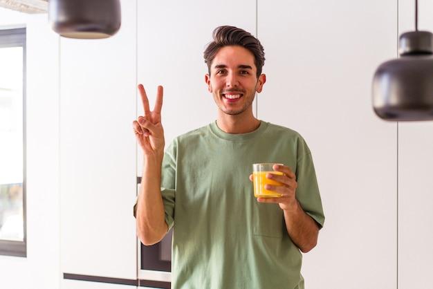 Jovem mestiço bebendo suco de laranja em sua cozinha, mostrando o número dois com os dedos.