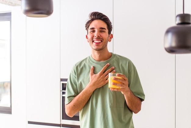 Jovem mestiço bebendo suco de laranja em sua cozinha ri alto, mantendo a mão no peito.