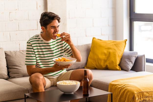 Jovem mestiço comendo pipoca sentado no sofá