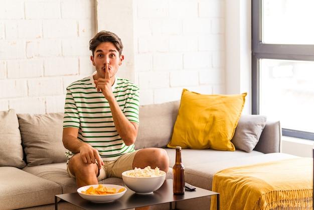 Jovem mestiço comendo pipocas, sentado no sofá, escondendo um segredo ou pedindo silêncio.