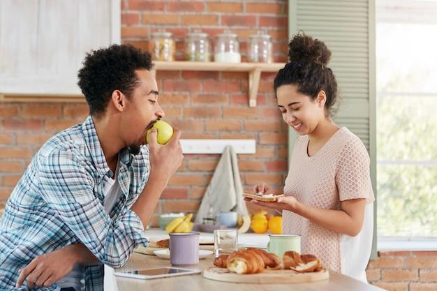 Jovem mestiço faminto come maçã enquanto espera quando sua esposa prepara o jantar. mulher bonita e cacheada que faz cobras