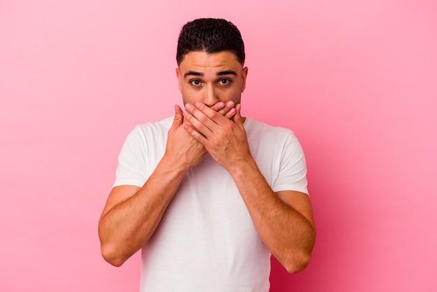 Jovem mestiço isolado em um fundo rosa chocado, cobrindo a boca com as mãos, ansioso para descobrir algo novo.