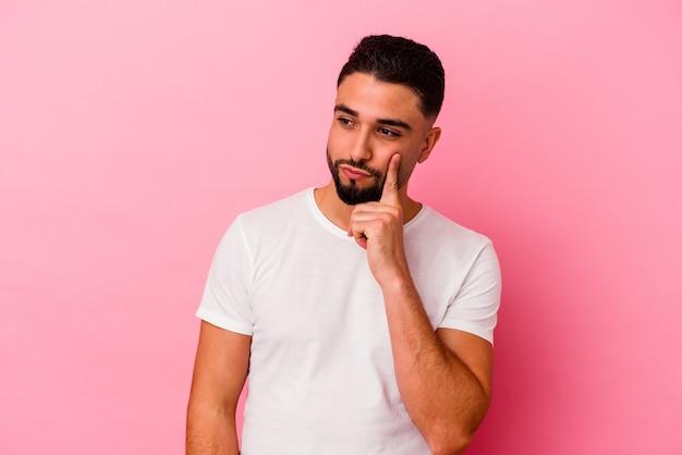Jovem mestiço isolado em um fundo rosa, contemplando, planejando uma estratégia, pensando no caminho de um negócio.