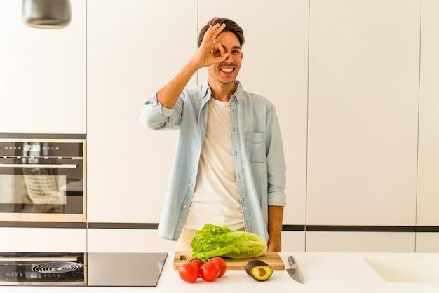 Jovem mestiço preparando uma salada para o almoço animado, mantendo o gesto de ok no olho.
