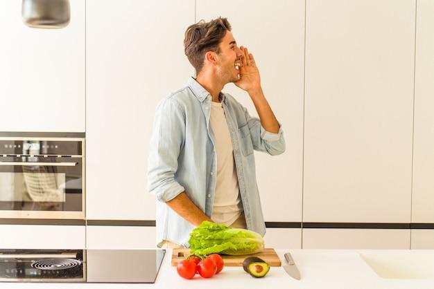 Jovem mestiço preparando uma salada para o almoço, gritando e segurando a palma da mão perto da boca aberta.