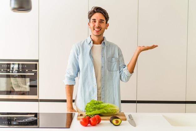 Jovem mestiço preparando uma salada para o almoço, mostrando um espaço de cópia na palma da mão e segurando a outra mão na cintura.