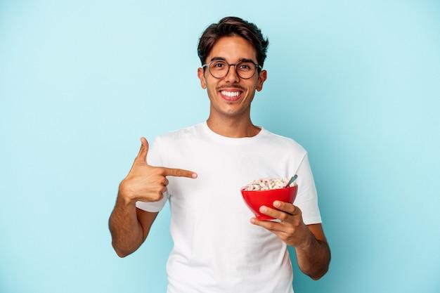 Jovem mestiço segurando cereais isolados em um fundo azul pessoa apontando com a mão para um espaço de cópia de camisa, orgulhoso e confiante