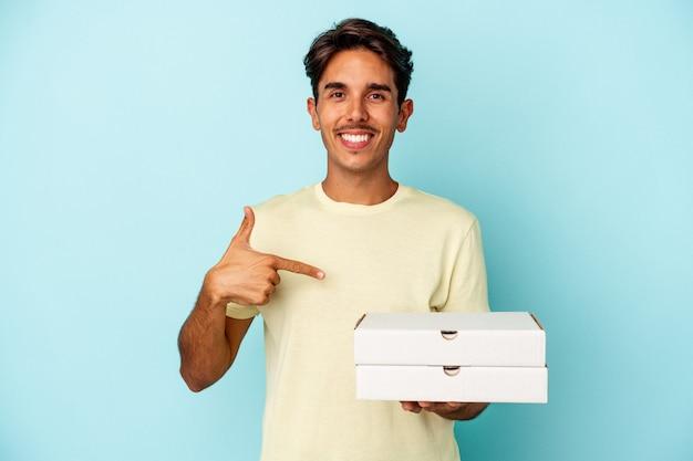 Jovem mestiço segurando pizzas isoladas em um fundo azul pessoa apontando com a mão para um espaço de cópia de camisa, orgulhoso e confiante
