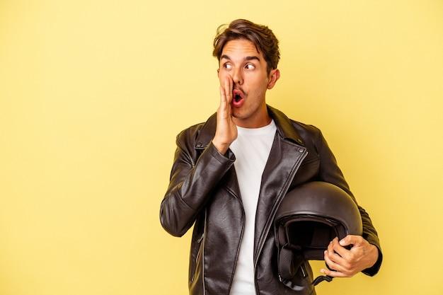 Jovem mestiço segurando um capacete isolado em um fundo amarelo está contando uma notícia secreta de travagem e olhando para o lado