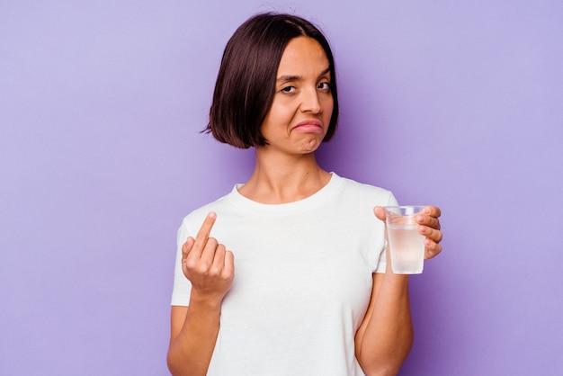 Jovem mestiço segurando um copo d'água isolado no fundo roxo, apontando com o dedo para você como se fosse um convite para se aproximar.
