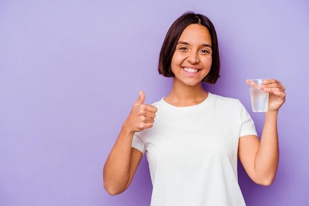 Jovem mestiço segurando um copo d'água isolado no fundo roxo, sorrindo e levantando o polegar