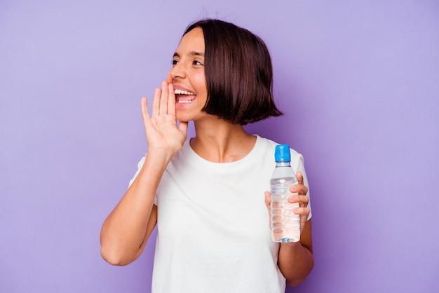 Jovem mestiço segurando uma garrafa de água isolada em um fundo roxo gritando e segurando a palma da mão perto da boca aberta.