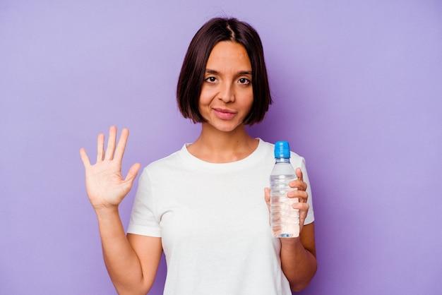Jovem mestiço segurando uma garrafa de água isolada no fundo roxo, sorrindo alegre mostrando o número cinco com os dedos.