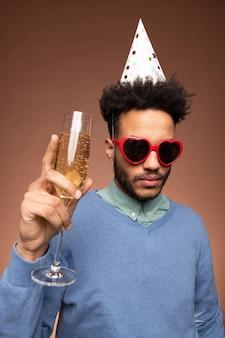 Jovem mestiço sério em trajes casuais elegantes, boné de aniversário e óculos de sol em forma de coração segurando uma taça de espumante champanhe