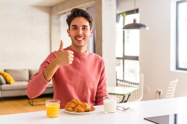 Jovem mestiço tomando café da manhã em uma cozinha, sorrindo e levantando o polegar