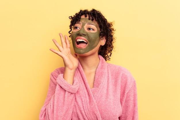 Jovem mestiço usando máscara facial isolada em fundo amarelo, gritando e segurando a palma da mão perto da boca aberta.