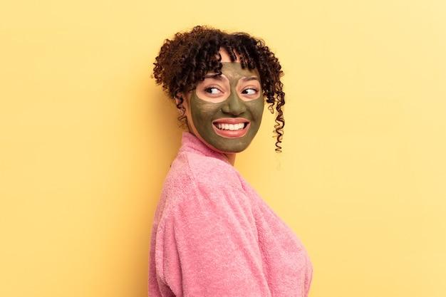 Jovem mestiço usando máscara facial isolada em fundo amarelo parece de lado sorrindo, alegre e agradável.