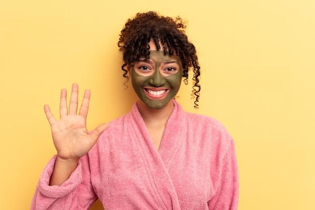 Jovem mestiço usando máscara facial isolada em fundo amarelo, sorrindo alegre mostrando o número cinco com os dedos.