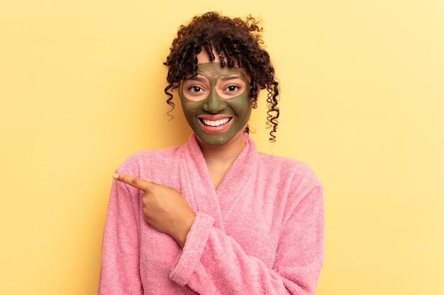 Jovem mestiço usando máscara facial isolada em fundo amarelo, sorrindo e apontando para o lado, mostrando algo no espaço em branco.