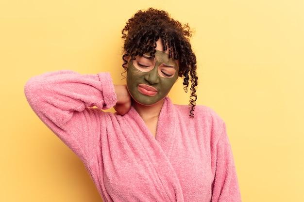 Jovem mestiço usando máscara facial isolada em fundo amarelo, tocando a nuca, pensando e fazendo uma escolha.