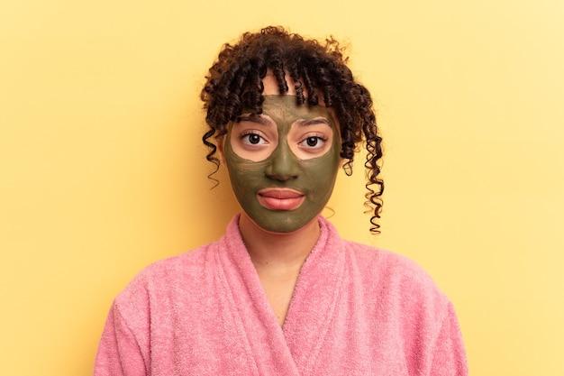Jovem mestiço usando máscara facial isolada em fundo amarelo