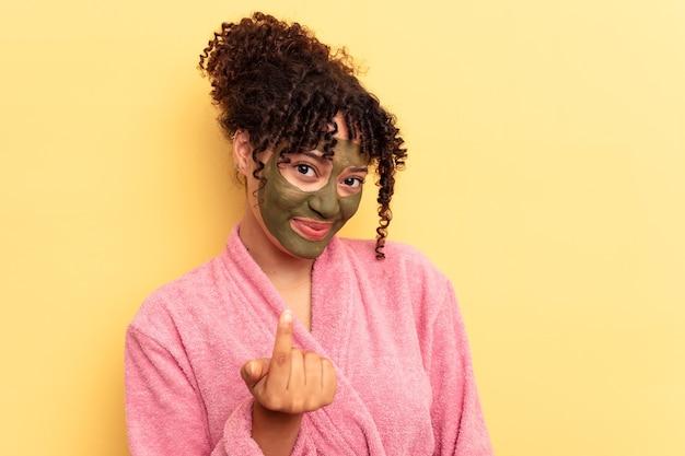 Jovem mestiço usando máscara facial isolada em um fundo amarelo apontando com o dedo para você como se fosse um convite para se aproximar.