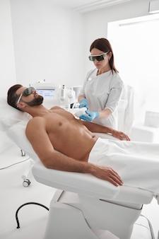 Jovem mestre com óculos de proteção realiza depilação a laser para cliente barbudo deitado no sofá