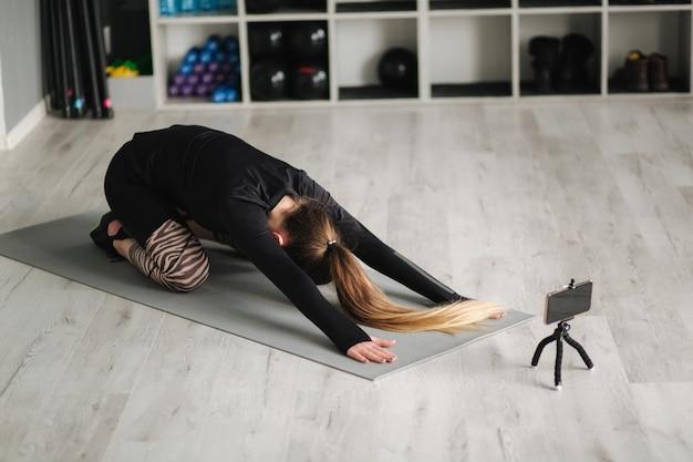 Jovem mestre de ioga gravando conteúdo de vídeo de seu exercício para seu curso online com o telefone no tripé. treinamento feminino atlético em estúdio.