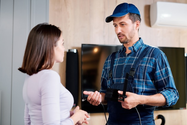 Jovem mestre em serviço de conserto de dispositivos domésticos, explicando a um dos clientes como usar o dispositivo durante a consulta
