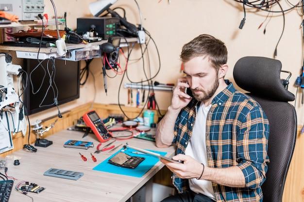 Jovem mestre profissional em serviço de conserto de gadgets conversando com um cliente no smartphone enquanto examina solicitações online no touchpad