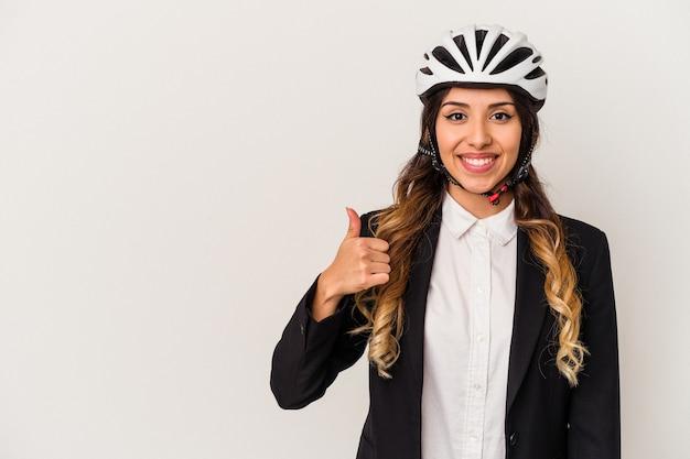 Jovem mexicana andando de bicicleta para trabalhar isolada no fundo branco sorrindo e levantando o polegar
