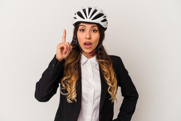 Jovem mexicana andando de bicicleta para trabalhar, isolada no fundo branco, tendo uma ideia, o conceito de inspiração.