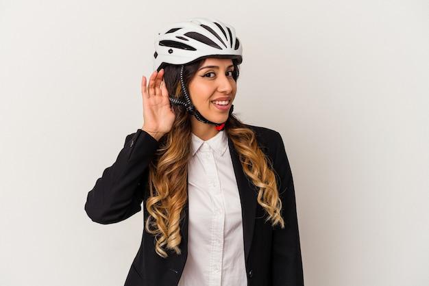 Jovem mexicana andando de bicicleta para trabalhar, isolada no fundo branco, tentando ouvir uma fofoca.