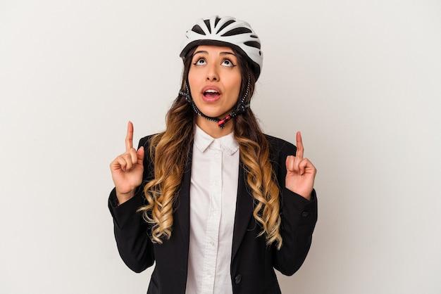 Jovem mexicana andando de bicicleta para trabalhar isolado no fundo branco, apontando de cabeça para baixo com a boca aberta.