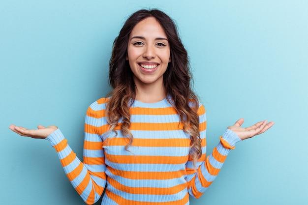 Jovem mexicana isolada em um fundo azul, mostrando uma expressão de boas-vindas.