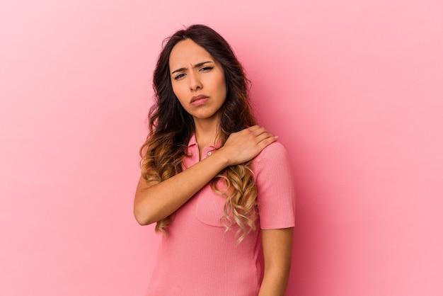 Jovem mexicana isolada em um fundo rosa, tendo uma dor no ombro.