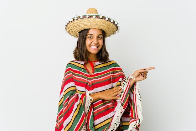 Jovem mexicana isolada na parede branca, sorrindo alegremente, apontando com o dedo indicador de distância.