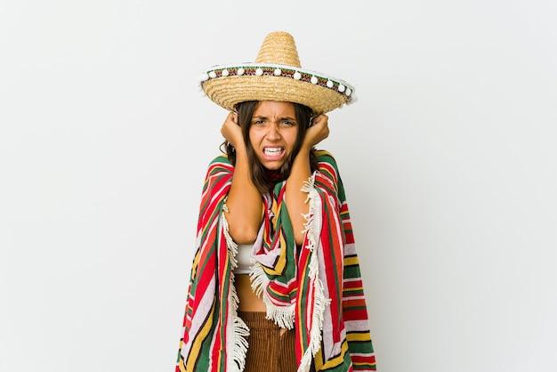 Jovem mexicana isolada no branco, cobrindo os ouvidos com as mãos, tentando não ouvir o som muito alto.