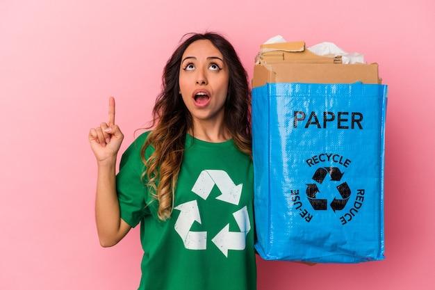 Jovem mexicana reciclando papelão isolado em um fundo rosa apontando para cima com a boca aberta.