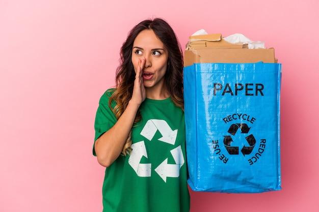Jovem mexicana reciclando papelão isolado em um fundo rosa está contando uma notícia secreta sobre a travagem e olhando para o lado