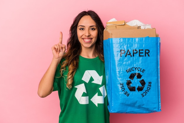Jovem mexicana reciclando papelão isolado no fundo rosa, mostrando o número um com o dedo.