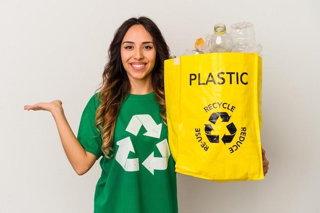 Jovem mexicana reciclando plástico isolado no fundo branco, mostrando um espaço de cópia na palma da mão e segurando a outra mão na cintura.