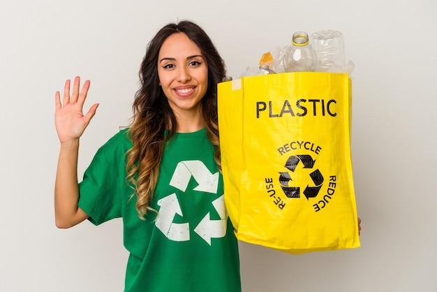 Jovem mexicana reciclando plástico isolado no fundo branco, sorrindo alegre mostrando o número cinco com os dedos.