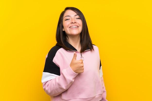 Jovem, mexicano, mulher, isolado, amarela, dar, um, polegares cima, gesto