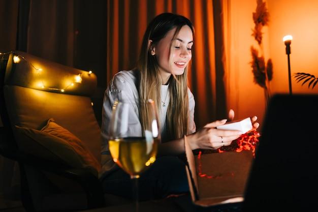 Jovem milenar aberto presente na frente do computador portátil durante a videochamada e bebendo vinho, usa a tecnologia para se comunicar com amigos ou família.