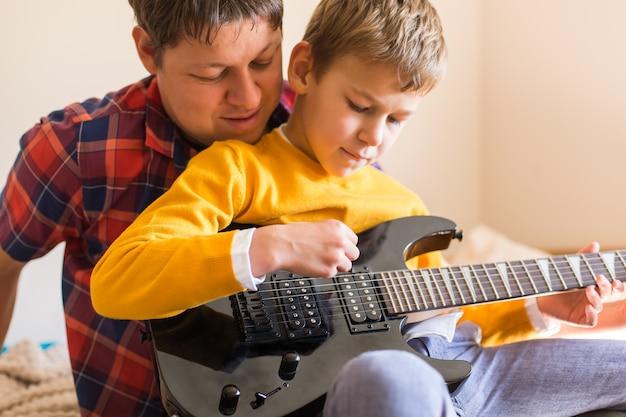 Jovem milenar, pai e filho bonito tocando guitarra elétrica. ficar em casa, atividades em casa, aulas de aprendizagem, família se divertindo momentos juntos