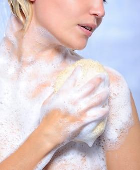 Jovem mimando o corpo com esponja e espuma de sabão