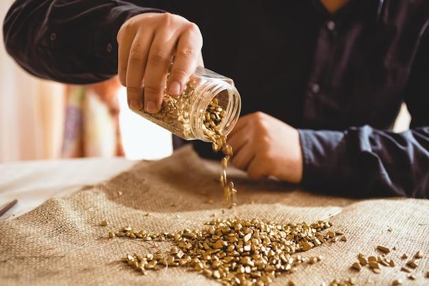 Jovem mineiro sentado à mesa e derramando ouro de uma jarra de vidro